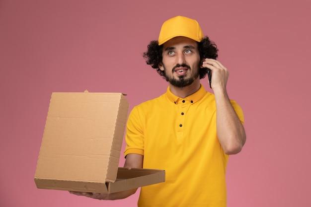 Courier masculino de uniforme amarelo segurando uma caixa de entrega de comida e falando ao telefone na parede rosa claro.