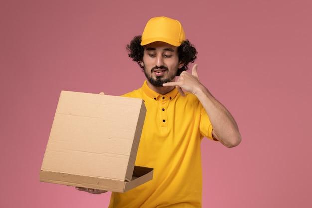 Courier masculino de uniforme amarelo segurando uma caixa de entrega de comida na mesa rosa claro.