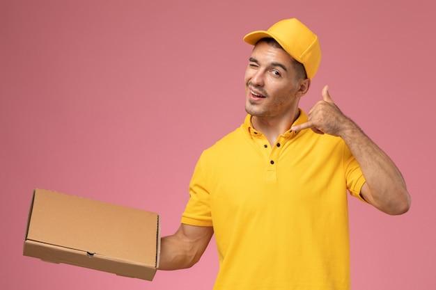 Courier masculino de uniforme amarelo segurando uma caixa de entrega de comida na mesa rosa