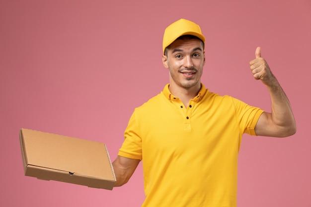 Courier masculino de uniforme amarelo segurando uma caixa de entrega de comida no fundo rosa