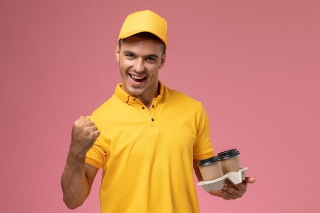 Courier masculino de uniforme amarelo segurando xícaras de café de entrega e regozijando-se no fundo rosa