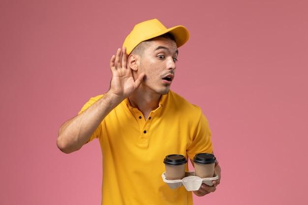 Courier masculino de uniforme amarelo segurando xícaras de café de entrega tentando ouvir na mesa rosa