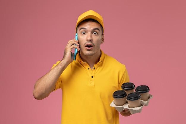 Courier masculino de uniforme amarelo segurando xícaras de café e falando ao telefone, surpreso na mesa rosa claro