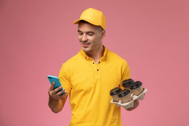 Courier masculino de uniforme amarelo segurando xícaras de café enquanto usa o telefone na mesa rosa