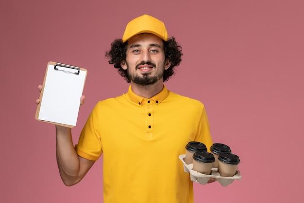 Courier masculino de uniforme amarelo segurando xícaras de café marrons e um bloco de notas na mesa rosa uniforme de trabalho masculino.