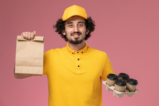 Courier masculino de uniforme amarelo segurando xícaras de café marrons e um pacote de comida na parede rosa