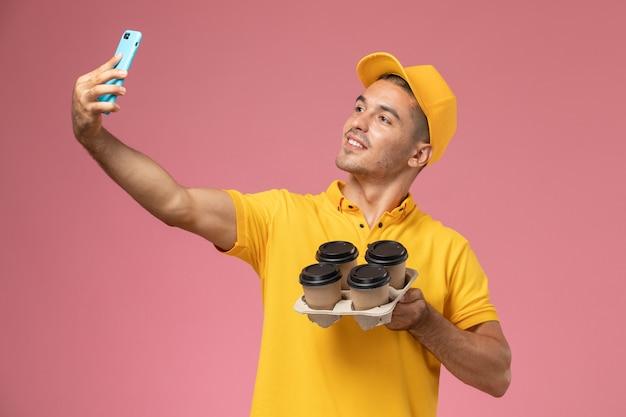 Courier masculino de uniforme amarelo segurando xícaras de café para entrega e tirando foto com eles na mesa rosa