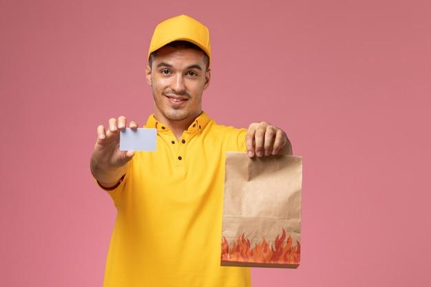 Courier masculino de uniforme amarelo, sorrindo, segurando um cartão cinza e um pacote de comida na mesa rosa
