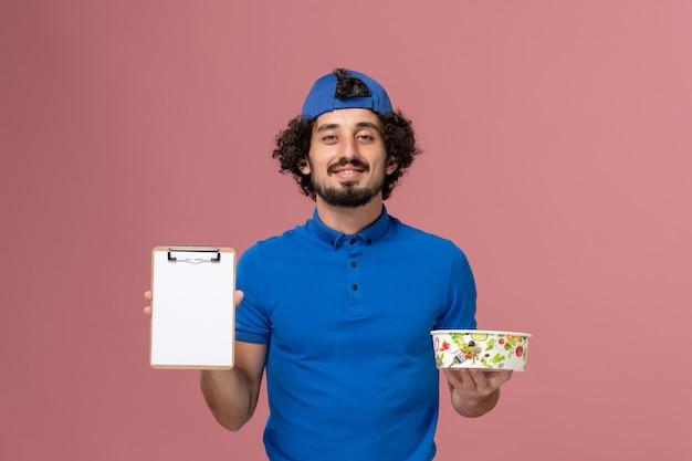 Courier masculino de uniforme azul e capa segurando o bloco de notas com tigela redonda na parede rosa