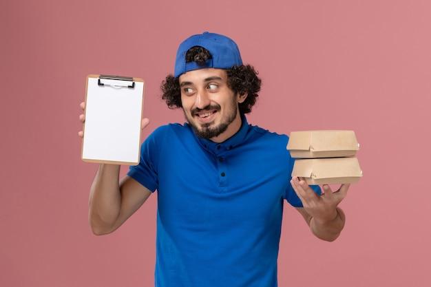 Courier masculino de uniforme azul e capa segurando pacotes de comida de entrega com bloco de notas na parede rosa. trabalho de serviço de entrega de uniforme