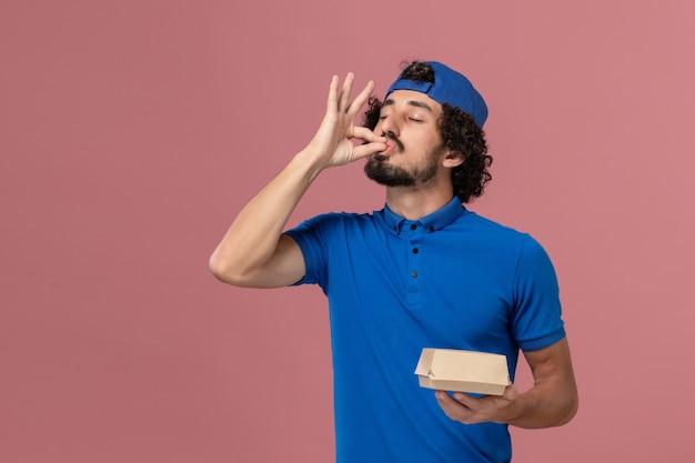 Courier masculino de uniforme azul e capa segurando um pequeno pacote de entrega de comida na parede rosa