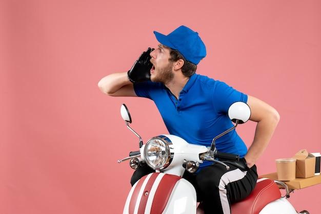 Courier masculino de uniforme azul ligando para alguém em comida rosa, entrega de bicicleta, trabalho de cor, serviço de fast-food