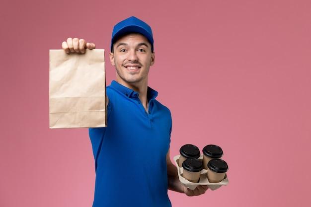 Courier masculino de uniforme azul segurando um pacote de comida com café na parede rosa, entrega de serviço de uniforme de trabalhador