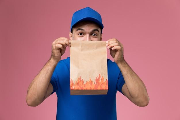Courier masculino de uniforme azul segurando um pacote de comida na parede rosa, entrega de serviço de uniforme de trabalhador