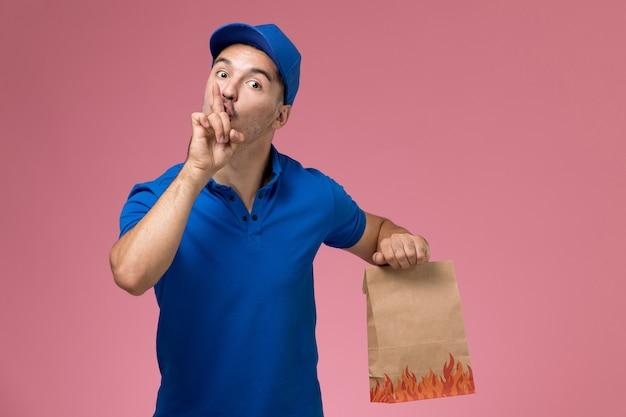 Courier masculino de uniforme azul segurando um pacote de comida pedindo para ficar em silêncio na parede rosa, entrega de serviço de uniforme de trabalhador de vista frontal