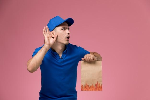 Courier masculino de uniforme azul segurando um pacote de papel e tentando ouvir na parede rosa, entrega de serviço de uniforme de trabalhador