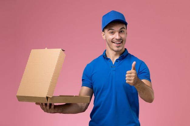 Courier masculino de uniforme azul segurando uma caixa de comida sorrindo na parede rosa, serviço de entrega de uniforme de trabalhador de vista frontal