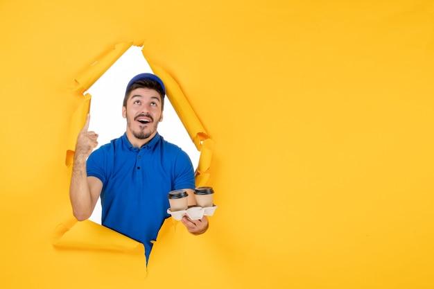 Courier masculino de uniforme azul segurando xícaras de café no espaço amarelo