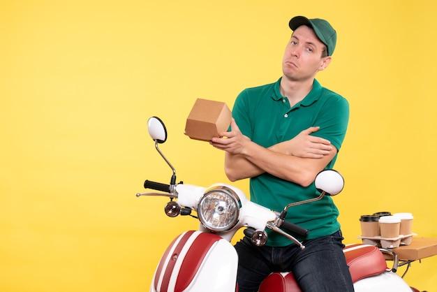 Courier masculino de uniforme segurando um pequeno pacote de comida em amarelo