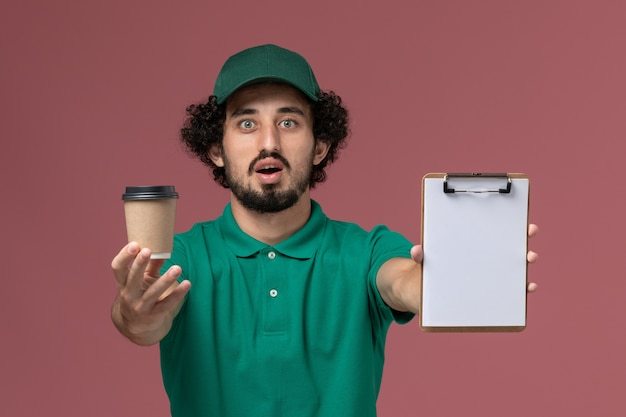 Courier masculino de uniforme verde e capa segurando a xícara de café de entrega com o bloco de notas na mesa rosa. trabalho de empresa de serviço de entrega uniforme