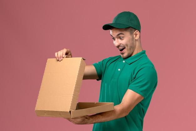 Courier masculino de uniforme verde segurando a caixa de comida e abrindo-a em fundo rosa