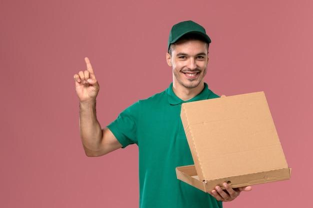 Courier masculino de uniforme verde segurando a caixa de comida e abrindo-a em um fundo rosa claro