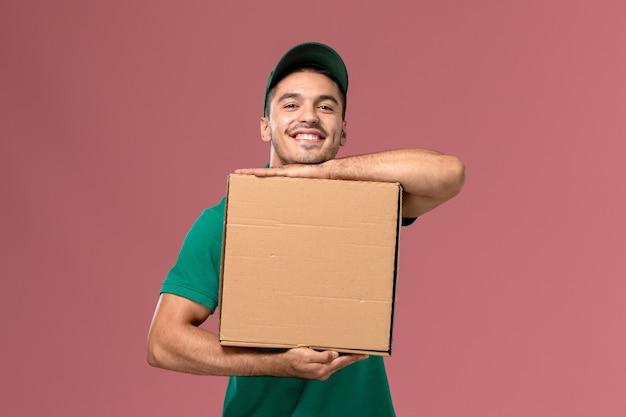 Courier masculino de uniforme verde segurando a caixa de comida e sorrindo na mesa rosa