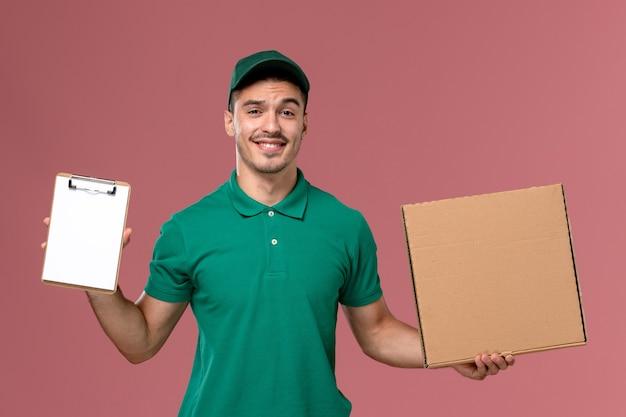 Courier masculino de uniforme verde segurando a caixa de comida junto com o bloco de notas na mesa rosa claro