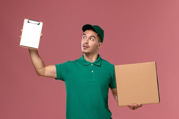 Courier masculino de uniforme verde segurando a caixa de comida junto com o bloco de notas no fundo rosa claro.