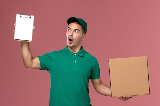 Courier masculino de uniforme verde segurando a caixa de comida junto com o bloco de notas no fundo rosa.