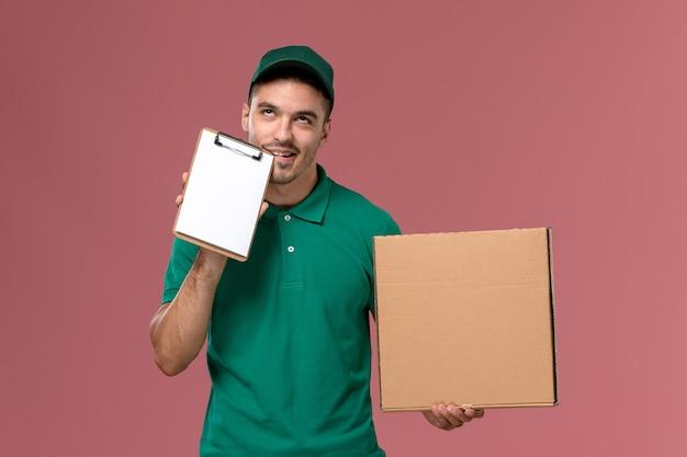 Courier masculino de uniforme verde segurando a caixa de comida junto com um pequeno bloco de notas no fundo rosa claro