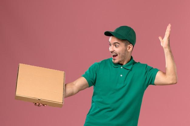 Courier masculino de uniforme verde segurando a caixa de comida na mesa rosa