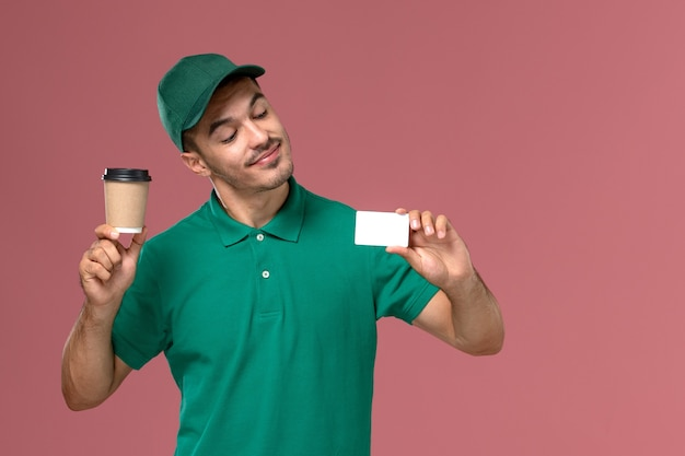 Courier masculino de uniforme verde segurando a xícara de café de entrega com cartão branco na mesa rosa