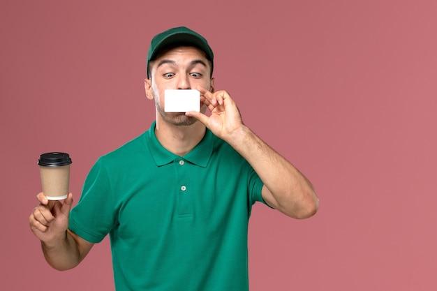 Courier masculino de uniforme verde segurando a xícara de café de entrega com cartão branco no fundo rosa claro.