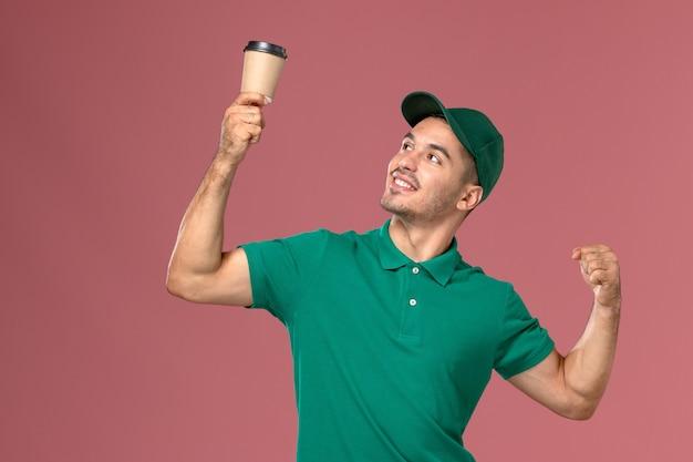 Courier masculino de uniforme verde segurando a xícara de café de entrega e flexionando na mesa rosa