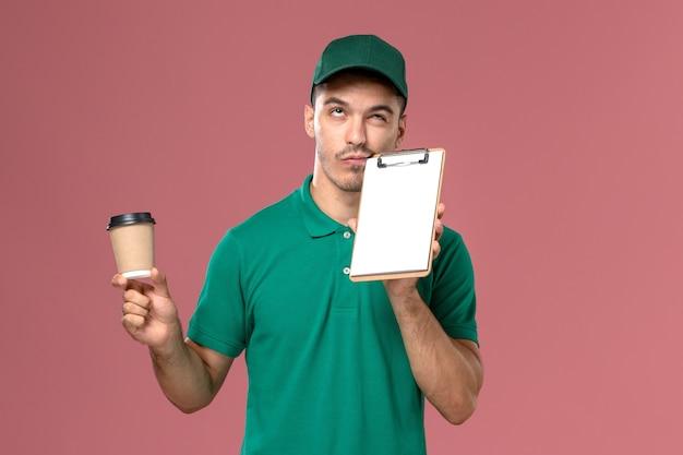 Courier masculino de uniforme verde segurando a xícara de café de entrega e o bloco de notas na mesa rosa claro