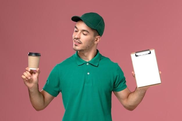 Courier masculino de uniforme verde segurando a xícara de café de entrega e o bloco de notas na mesa rosa