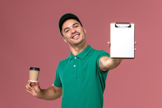 Courier masculino de uniforme verde segurando a xícara de café de entrega e o bloco de notas sorrindo na mesa rosa claro
