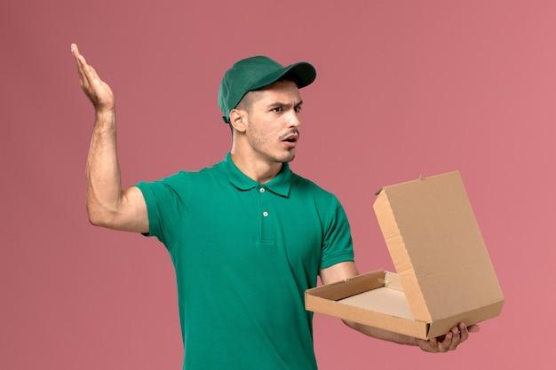 Courier masculino de uniforme verde segurando e abrindo a caixa de comida com expressão de descontentamento no fundo rosa