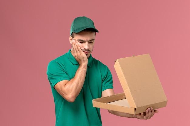 Courier masculino de uniforme verde segurando e abrindo a caixa de comida com expressão estressada em fundo rosa claro.