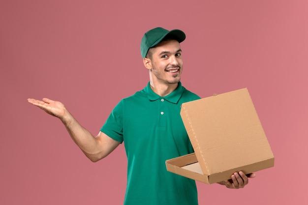 Courier masculino de uniforme verde segurando e abrindo a caixa de comida com um sorriso no fundo rosa claro.