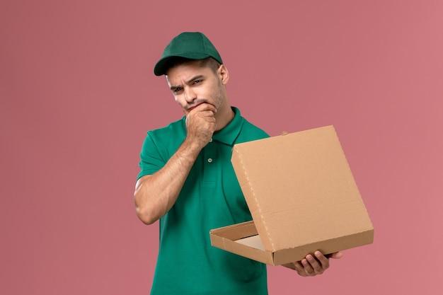 Courier masculino de uniforme verde segurando e abrindo a caixa de comida enquanto pensa no fundo rosa