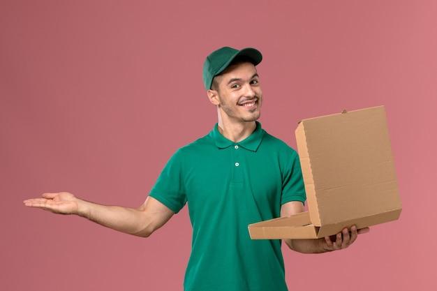 Courier masculino de uniforme verde segurando e abrindo a caixa de comida no fundo rosa claro