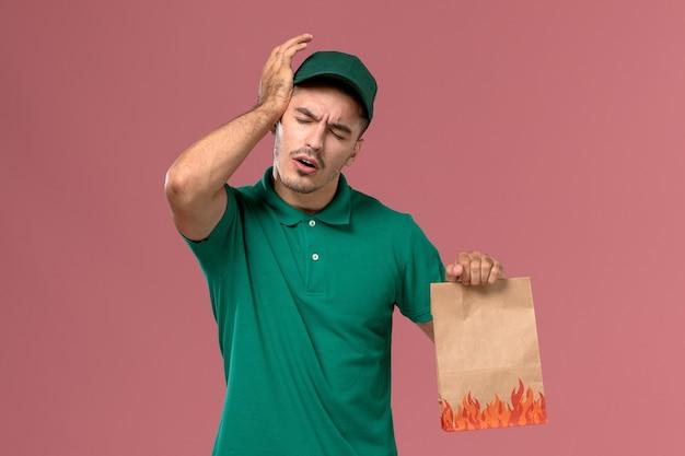 Courier masculino de uniforme verde segurando um pacote de comida de papel com dor de cabeça em fundo rosa claro