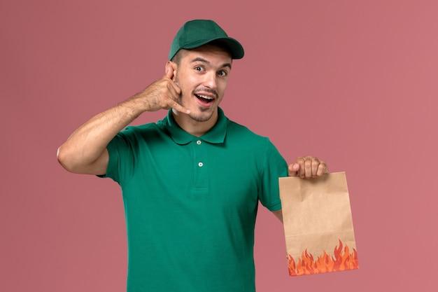 Courier masculino de uniforme verde segurando um pacote de comida de papel no fundo rosa claro.