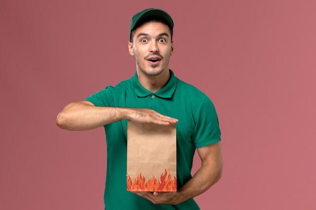 Courier masculino de uniforme verde segurando um pacote de comida de papel no fundo rosa