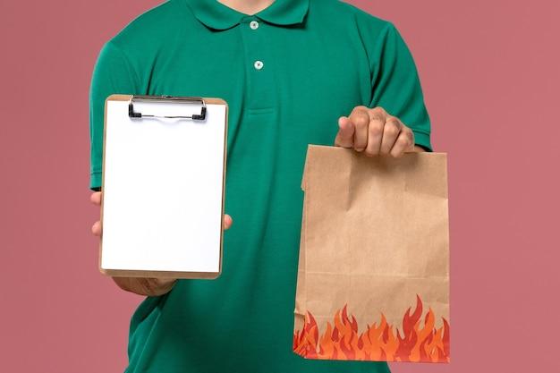 Courier masculino de uniforme verde segurando um pacote de comida e um bloco de notas em um fundo rosa claro