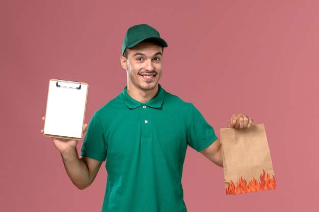 Courier masculino de uniforme verde segurando um pacote de comida e um bloco de notas no fundo rosa