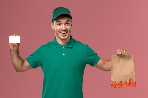 Courier masculino de uniforme verde segurando um pacote de comida e um cartão sorrindo no fundo rosa