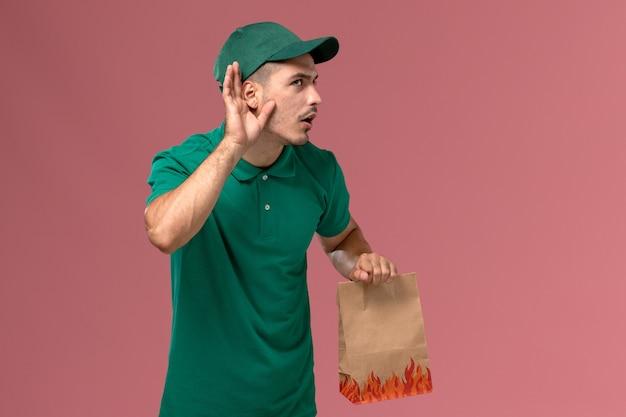 Courier masculino de uniforme verde segurando um pacote de papel para comida tentando ouvir sobre um fundo rosa claro